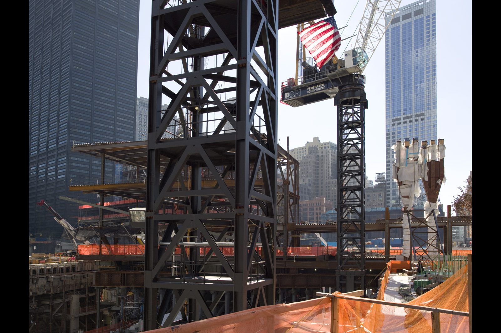 Looking from the same vantage point at street level in November, across the site of the new transit hub, Meyerowitz saw the flag hanging from the crane and recalled the shot he had made almost nine years earlier. Two tridents from the original World Trade Center construction appear in their temporary location at right — they will be permanently installed as part of the memorial