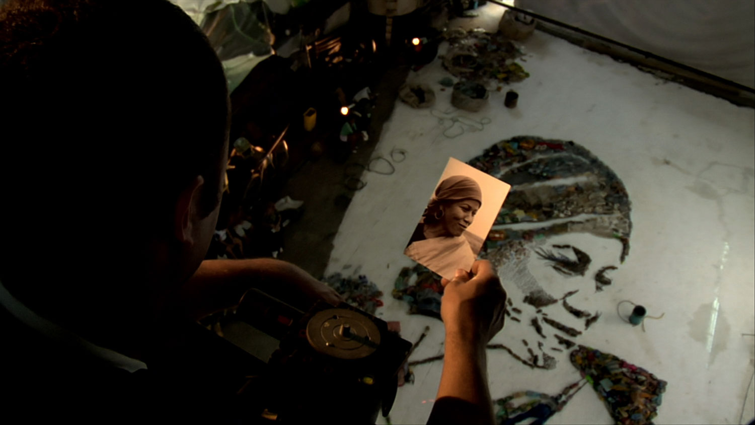 A scene from the film in which Muniz looks at Magna's photo while her final portrait is created in the studio