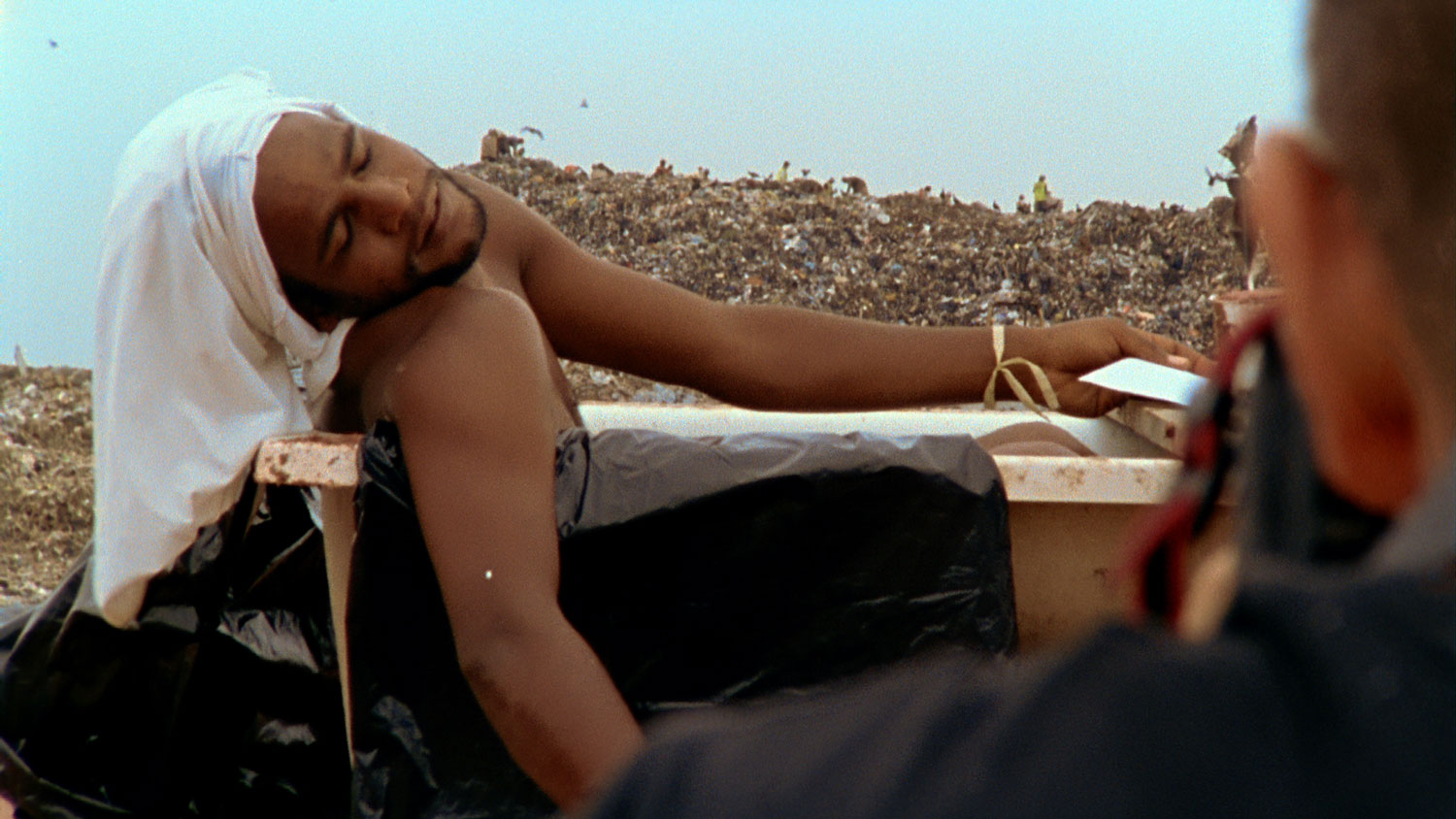 A scene from the film in which Muniz takes a photo of Tiao, inspired by a painting of Marat at Jardim Gramacho