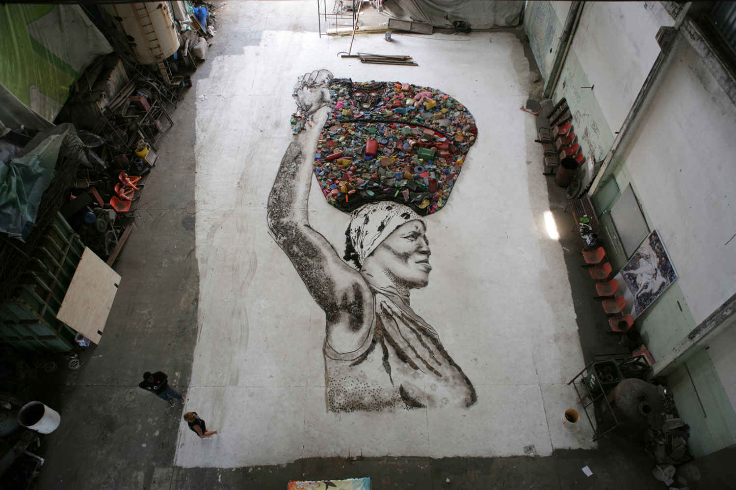 The portrait of Irma is created on the floor of the studio by Muniz and the workers of Jardim Gramacho. Once complete, the final portrait will be photographed from above by Muniz