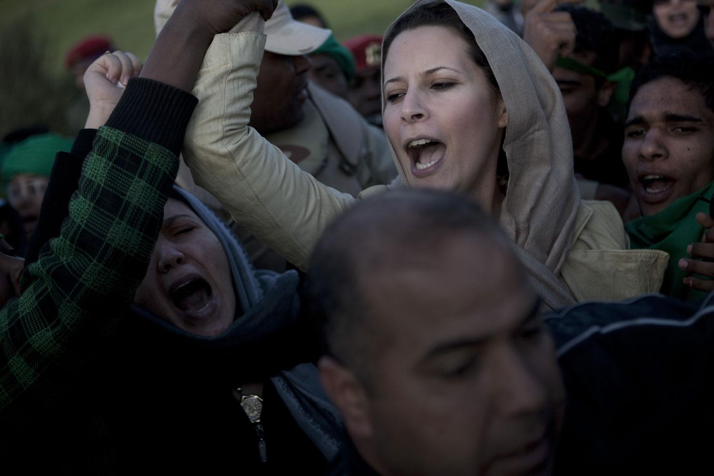 Ayesha Gaddafi, the daughter of Muammar Gaddafi, joins loyalist supporters at a rally outside Gaddafi's compound, March 19, 2011.