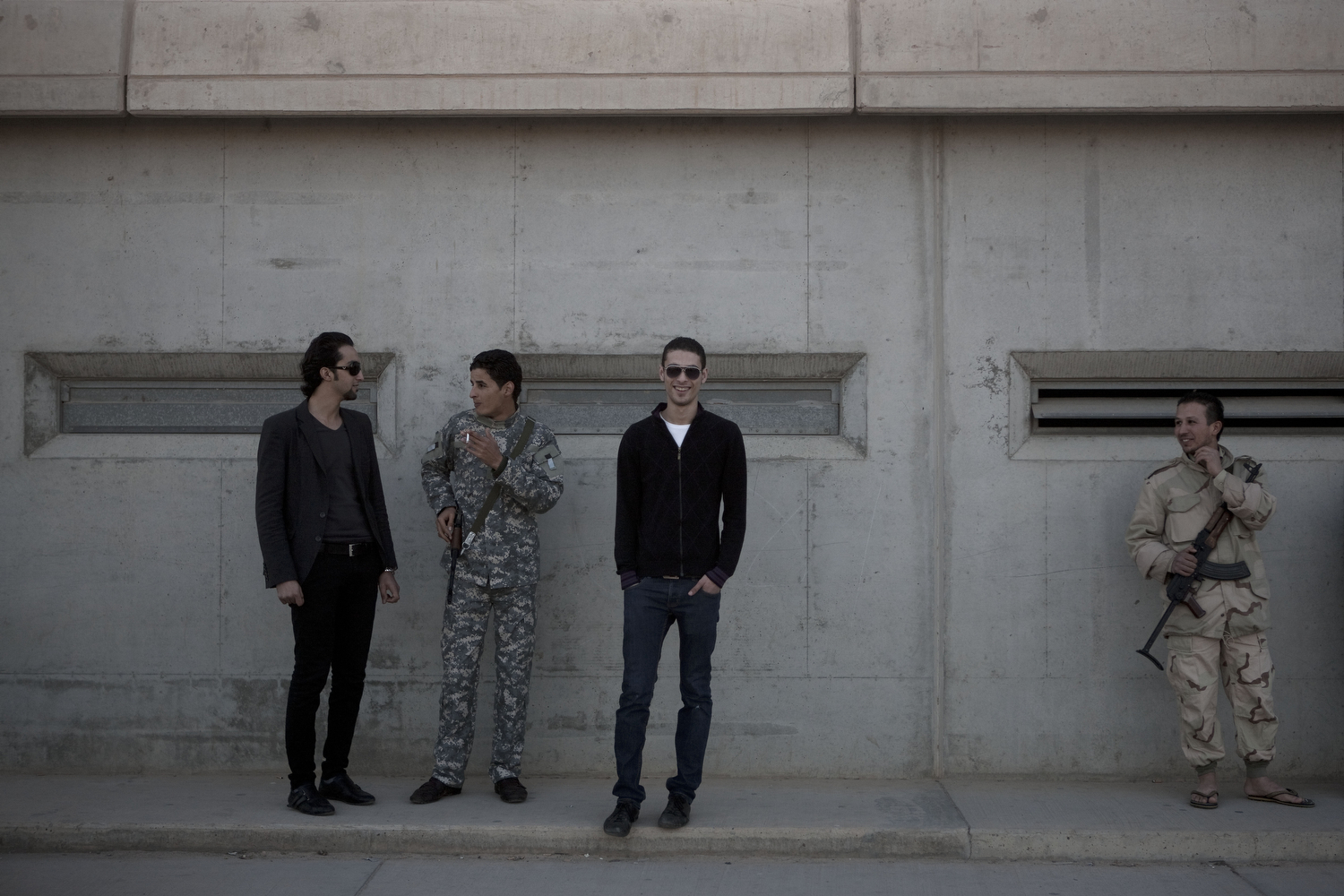 Men and soldiers chat near the blast wall outside of Gaddafi's compound, March 19, 2011.