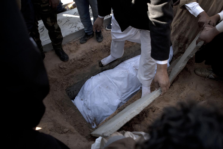 Gaddafi loyalists bury a man allegedly killed during a missile attack, March 20, 2011.
