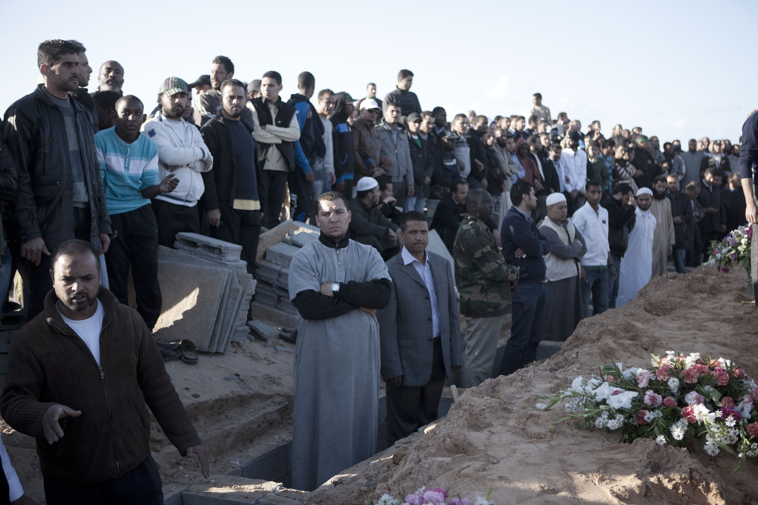 Men stand in prepared graves as they await the arrival of people allegedly killed during missile strikes, March 20, 2011.