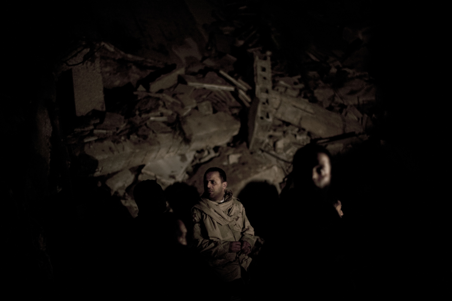 Libyan soldiers survey the damage to a building hit by a missile in Gaddafi's compound, March 21, 2011.