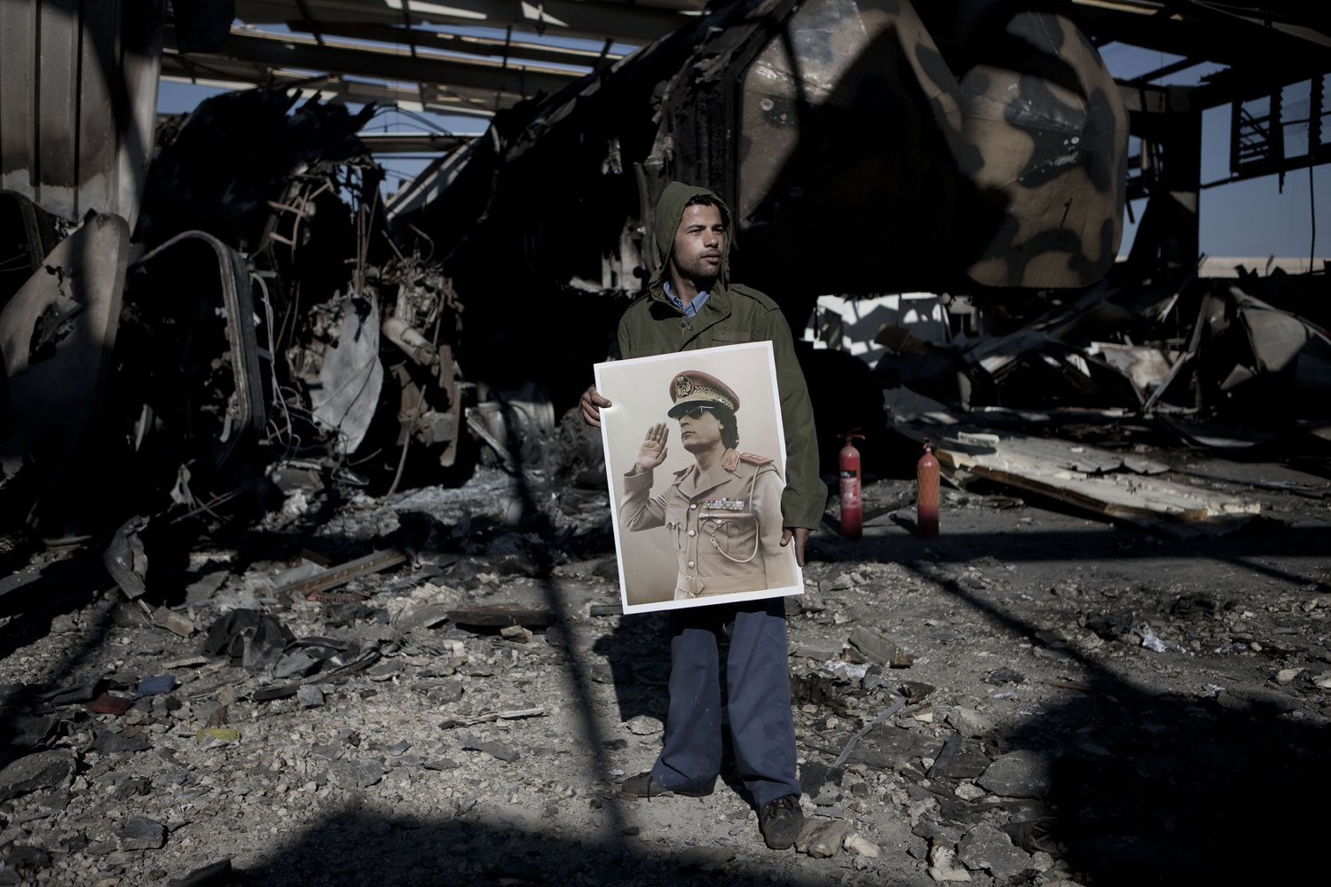A Gaddafi supporter holds a portrait of the Libyan leader for the media during a tour of a building struck by missiles, March 22, 2011.