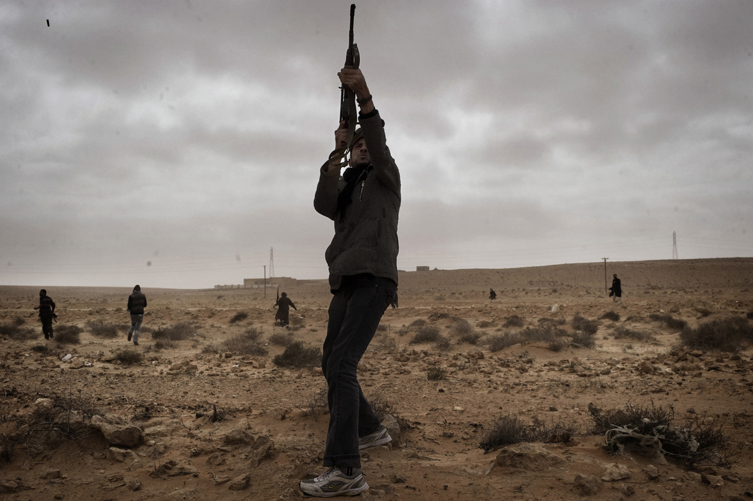 A rebel fires towards a Libyan government helicopter during a firefight in Bin Jawad, March 5, 2011.