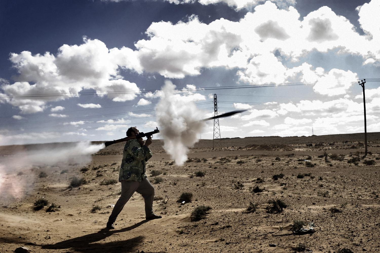 A rebel fires a rocket propelled grenade at Libyan troops near the frontline near Bin Jawad, March 6, 2011.
