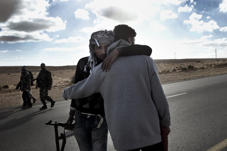 Libyan rebels embrace after retreating near Bin Jawad, March 6, 2011.