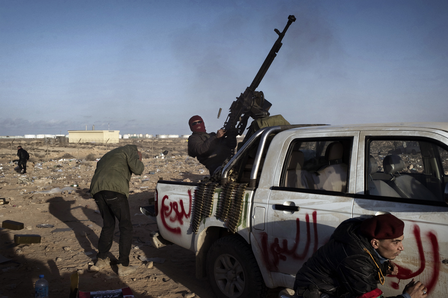 Rebels fire an anti-aircraft gun at Libyan jets near a checkpoint in Ras Lanuf, March 7, 2011.