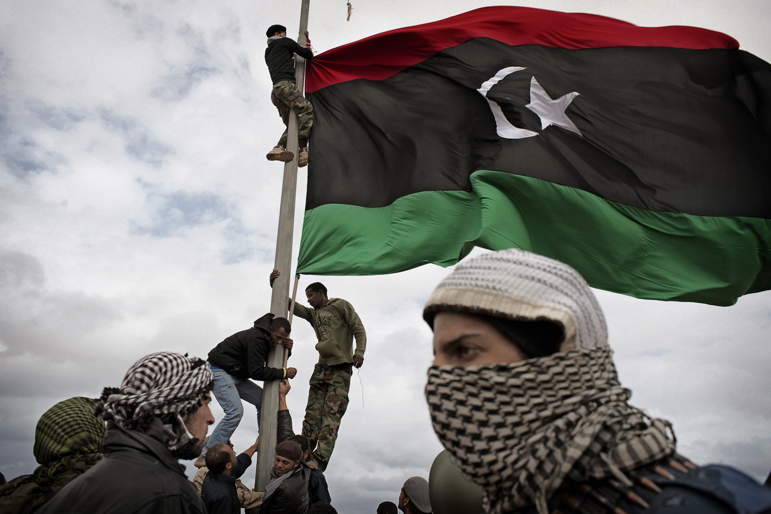 Libyan rebels raise their flag at a checkpoint in Ras Lanuf, March 8, 2011.