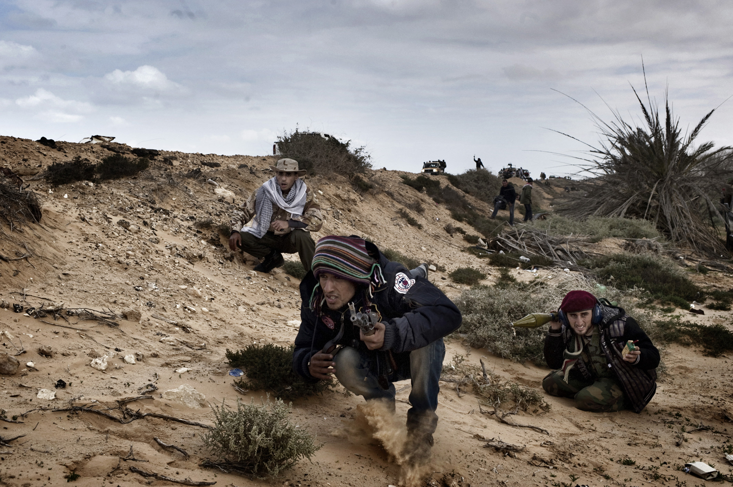Rebels take cover while battling government troops in Ras Lanuf, March 9, 2011.