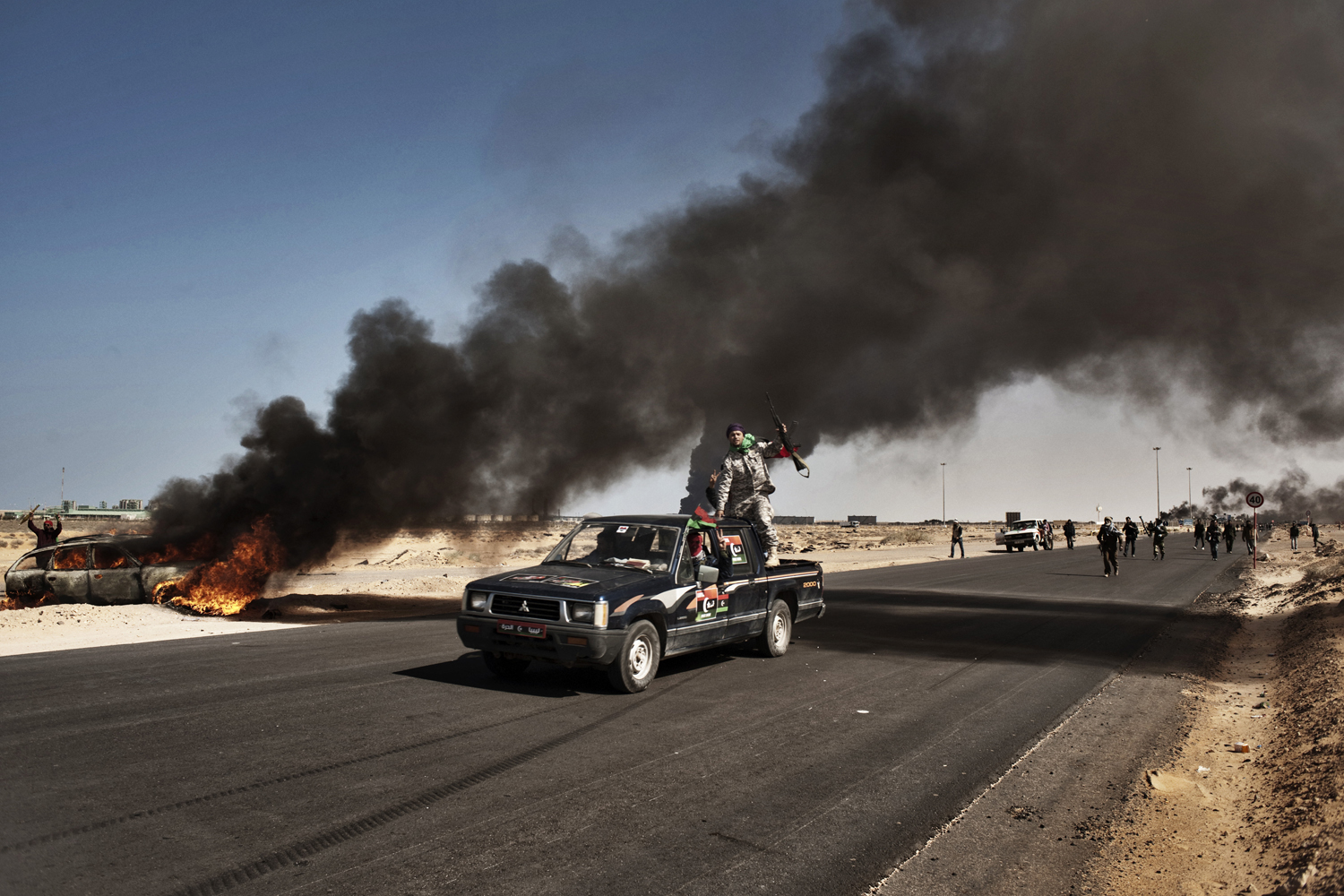 Rebels move across the battlefield near the oil town of Ras Lanuf, March 11, 2011.