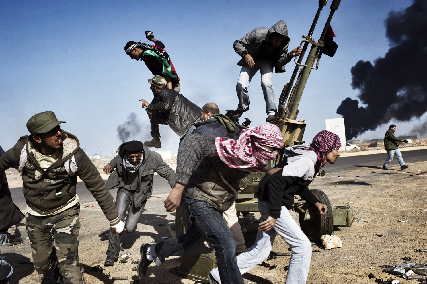 Rebels flee under fire from the Libyan army in Ras Lanuf, March 11, 2011.