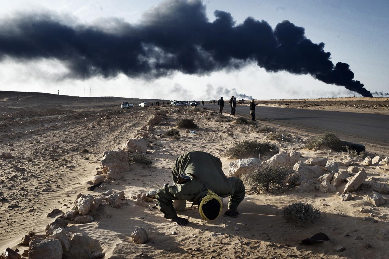 A damaged oil facility burns as a man prays in Ras Lanuf, March 11, 2011.