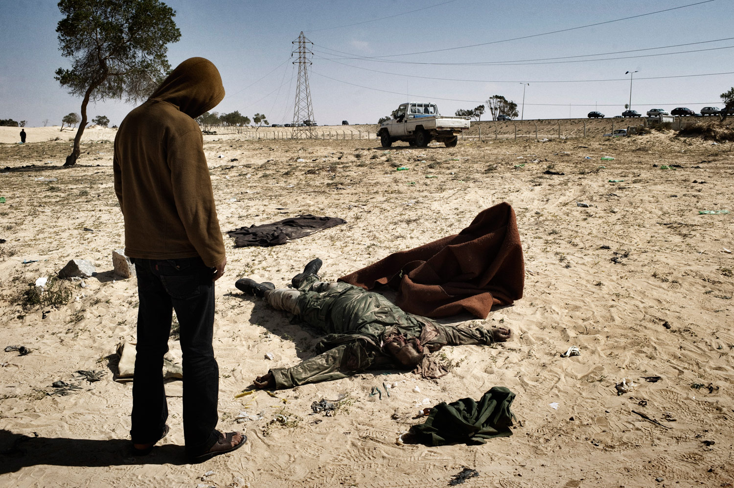 A Libyan rebel stands over the dead body of a Gaddafi soldier killed during an allied airstrike, March 26, 2011.