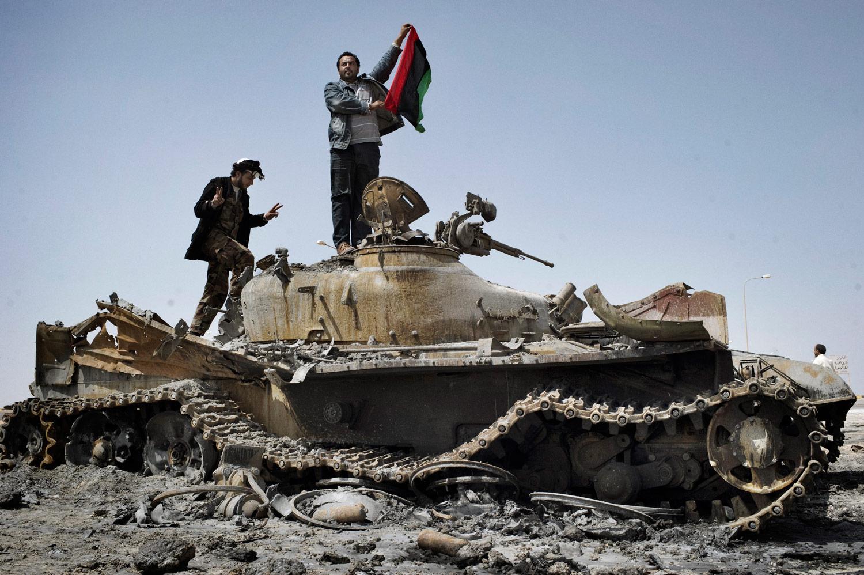 Libyan rebels celebrate on top of a Gaddafi loyalist tank outside of Ajdabiyah, March 26, 2011.