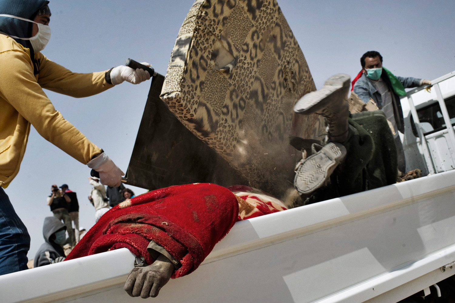Libyan rebels collect the bodies of dead Gaddafi soldiers killed during allied airstrikes, March 26, 2011.