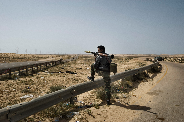 A Libyan rebel surveys the landscape near Brega, March 26, 2011.
