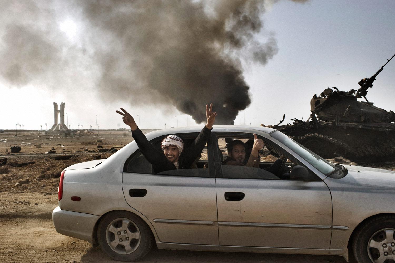Libyan rebels celebrate the retaking of Ajdabiyah near a smoldering tank, March 26, 2011.