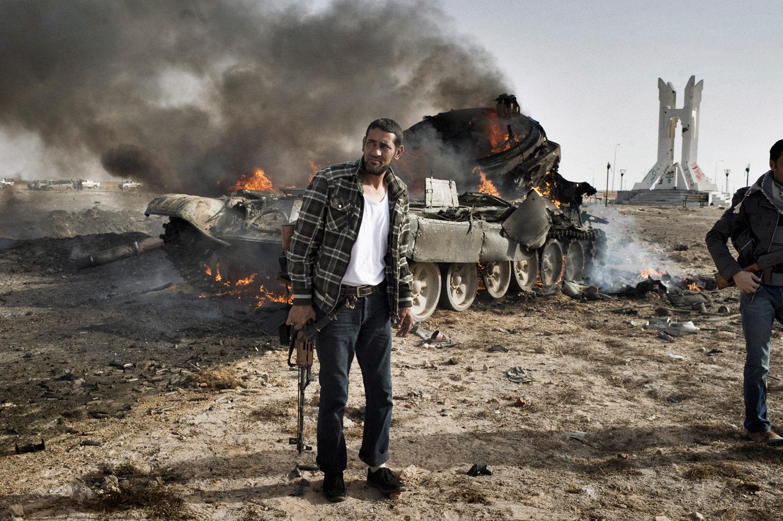 Libyan rebels near a destroyed Gaddafi tank near Ajdabiyah, March 26, 2011.
