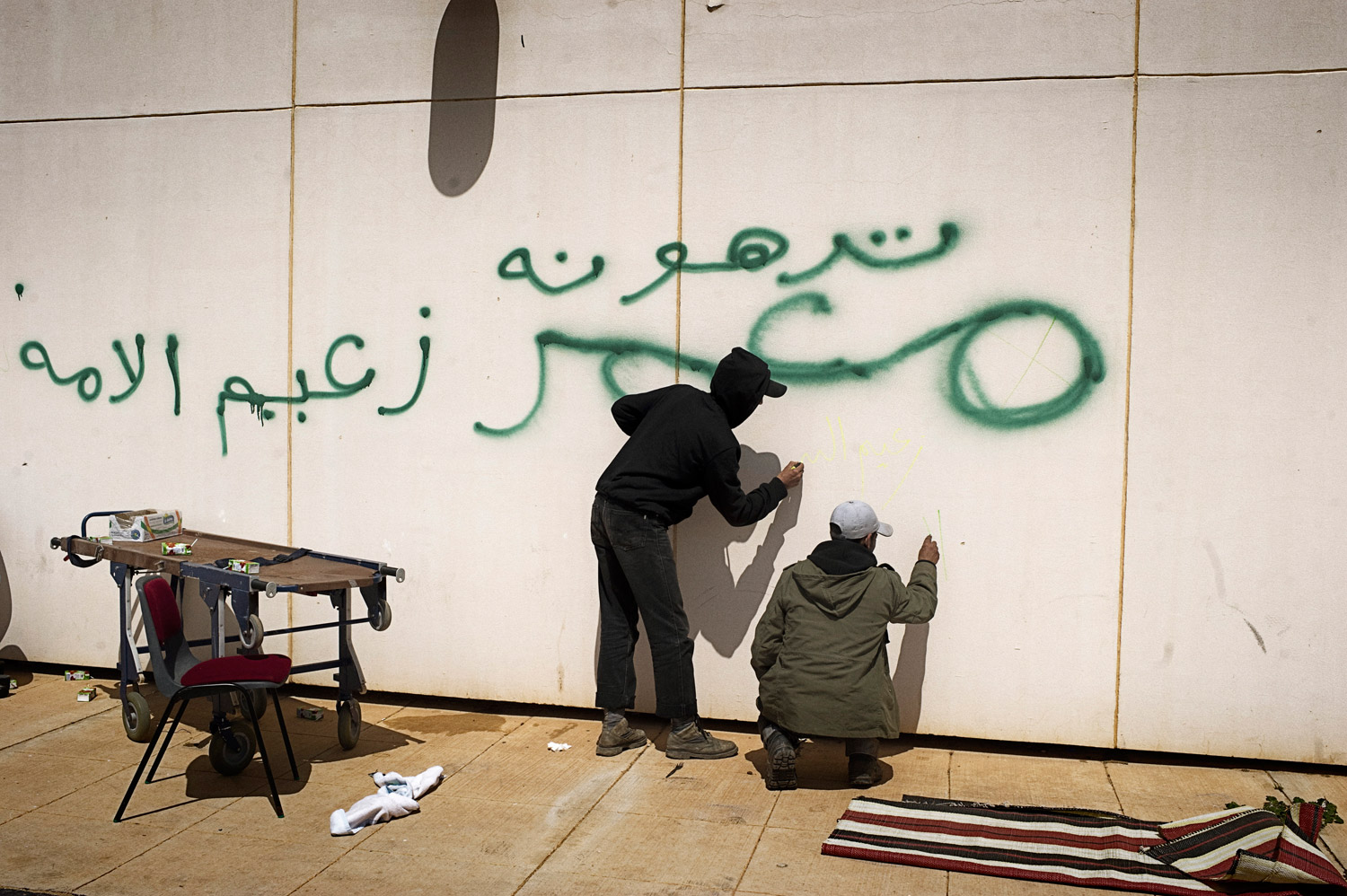 Libyan rebels scrawl graffiti on a wall near a hospital in Ras Lanuf, March 27, 2011. The wall was previously defaced, in green, by Gaddafi troops.