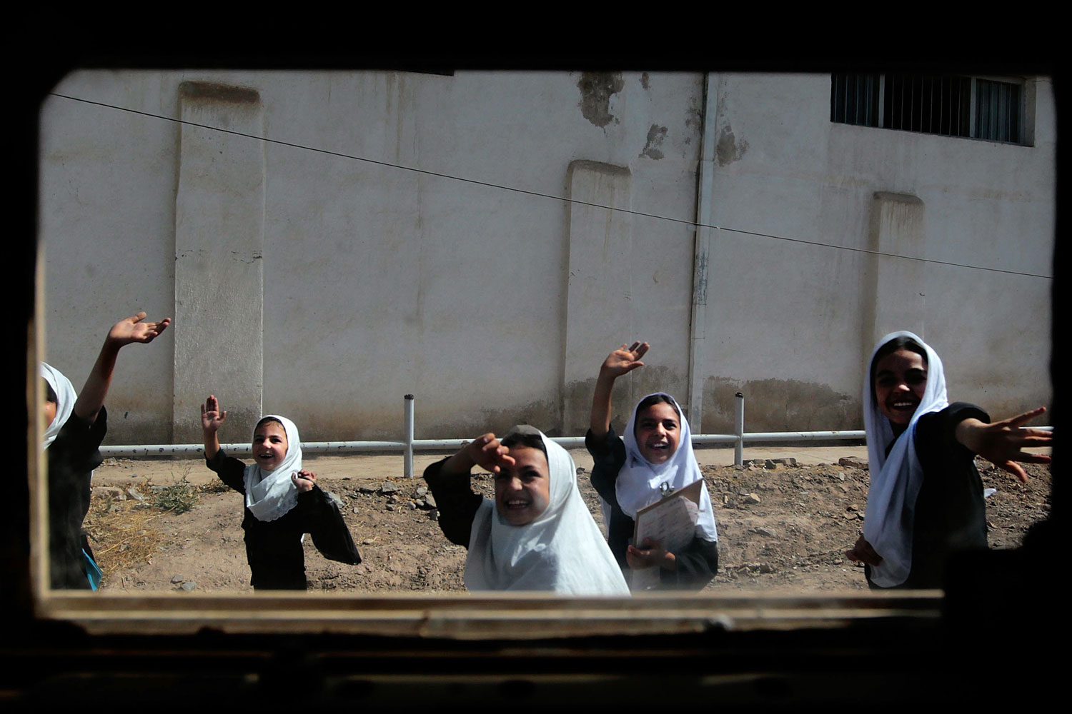 "Herat, Afghanistan, June 26, 2010: Afghan schoolgirls  wave to a passing American convoy. From the series ""Iraq and Afghanistan through a HumVee window""."