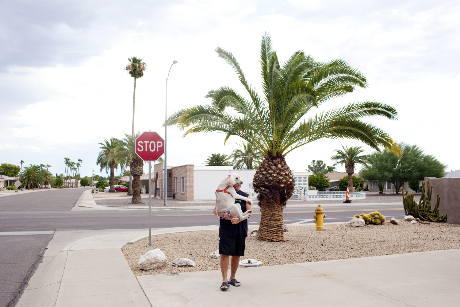 Bill Pearson, 62, with his standard poodle Phoenix stands outside of his home in Sun City, Arizona.