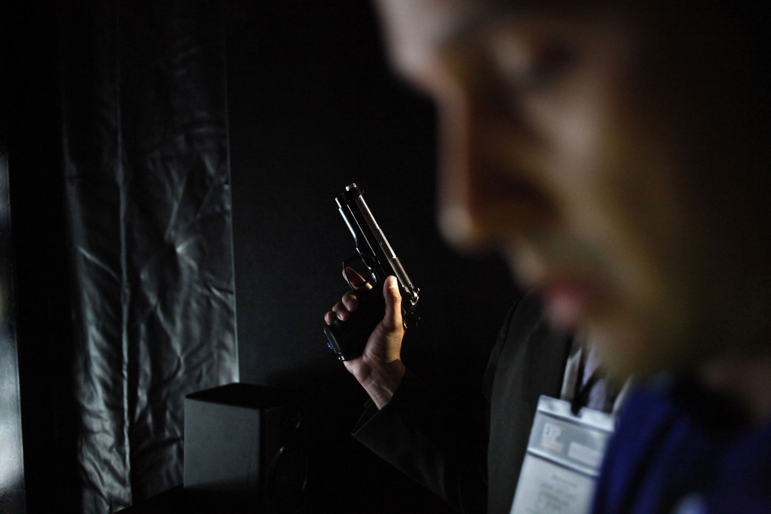 April 12, 2011. A visitor holds a pistol during the Expo Seguridad Mexico 2011 security fair in Mexico City. The fair displays the latest in police, civil defense and security equipment.