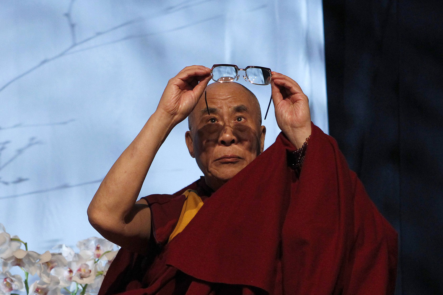 April 13, 2011. Tibet's exiled spiritual leader, the Dalai Lama, cleans his glasses during a press conference in Dublin. The Dalai Lama is on a two-day visit to Ireland.