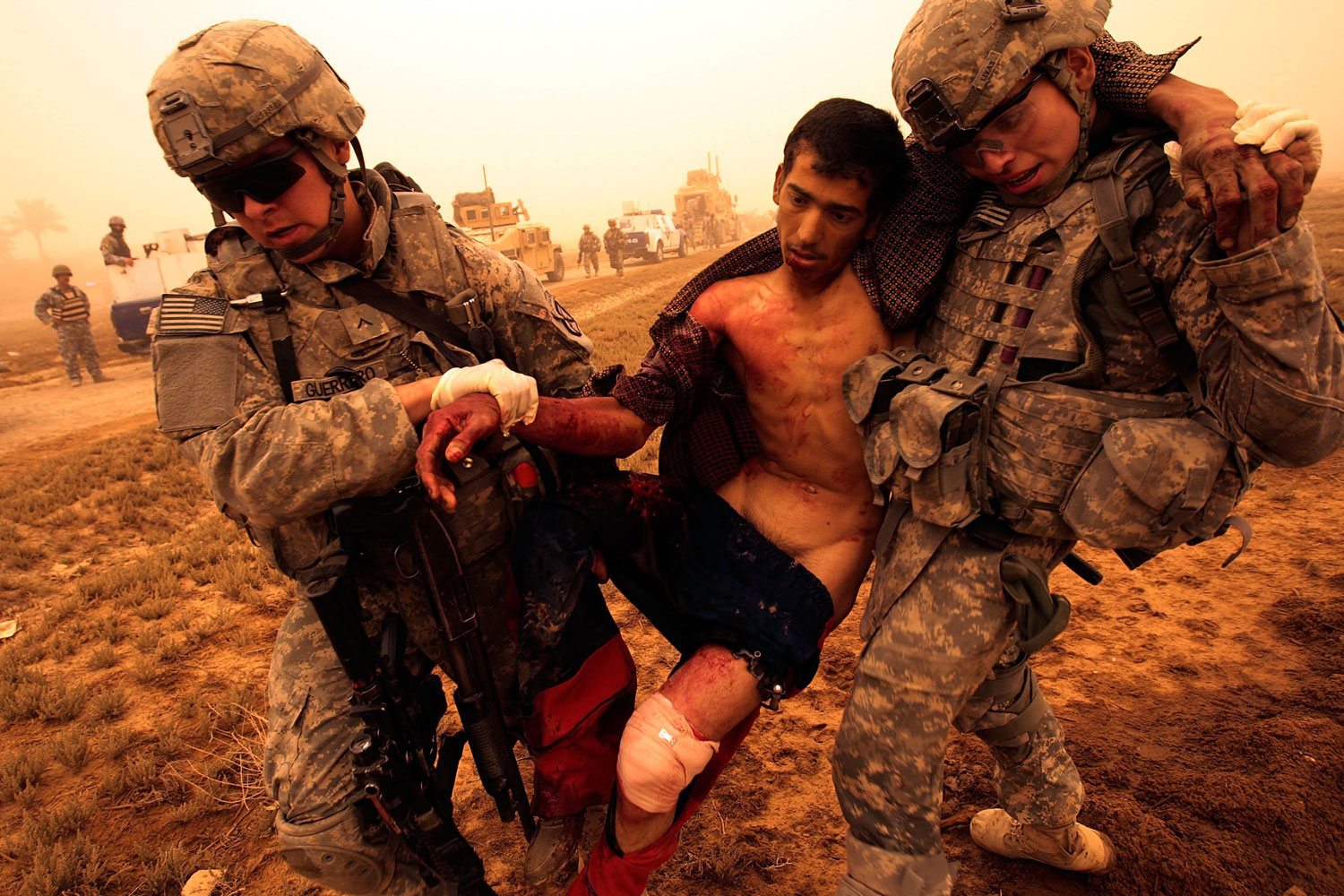 Baghdad, Iraq, May 16, 2008:  In the orange fog of an Iraqi sandstorm, PFC. Joshua Guerrero (L) and Private Aaron Livas, US troops of the 2nd Battalion, 30th Infantry Regiment of the 10th Mountain Division carry a wounded Iraqi man who started running from their platoon during a routine morning patrol and was shot.