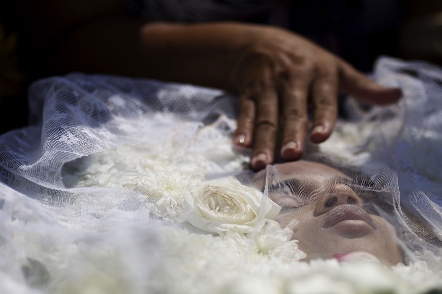 April 8, 2011. A relative mourns over the body of 14-year-old Luiza Paula da Silveira Machado during her funeral at the Jardim da Saudade cemetery in Rio de Janeiro, Brazil. Brazilian families began burying the 12 children gunned down in the halls of their elementary school Thursday. Luiza is one of ten girls and two boys between the ages of 12 and 15 who were killed by 23-year-old Wellington Oliveira, who shot and killed himself after being confronted by police.