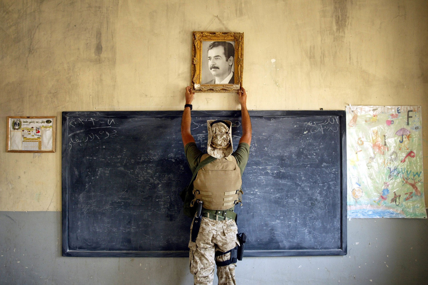 Al-Kut, Iraq  April 16 2003:  A U.S. Marine pulls down a picture of Saddam Hussein at a school. A combination team of Marines, Army and Special Forces went to schools and other facilities in Al-Kut looking for weapons caches and unexploded bombs.
