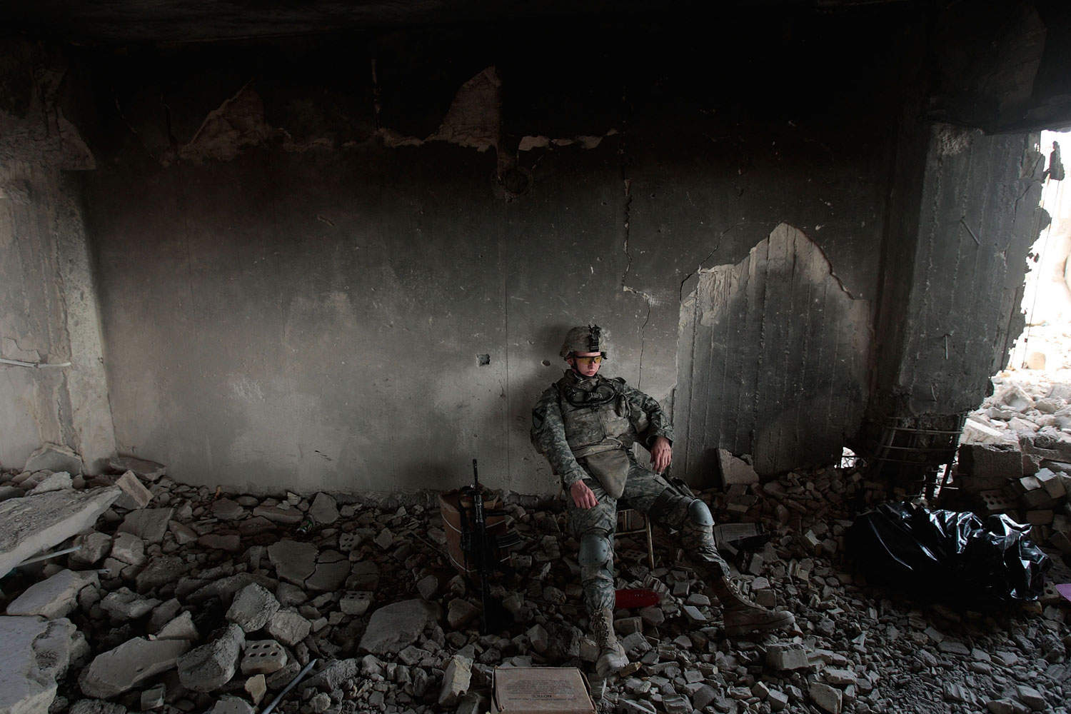 Baghdad, Iraq, July 13, 2007:  Pft. Daniel Sims of Clemson, South Carolina of the 1st Battalion, 5th Cavalry Regiment of the U.S. Army sits during watch duties in a partially destroyed building that's being converted to an Army field post in the tense Amariyah neighborhood of Baghdad, Iraq.