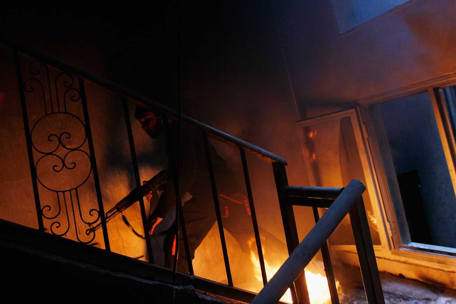 Misratah Libya April 20, 2011: A libyan rebel fighter runs up a burning stairwell during an effort to dislodge ensconced troops loyal to Moammar Gaddafi during house-to-house fighting on Tripoli Street in downtown Misratah, Libya.
