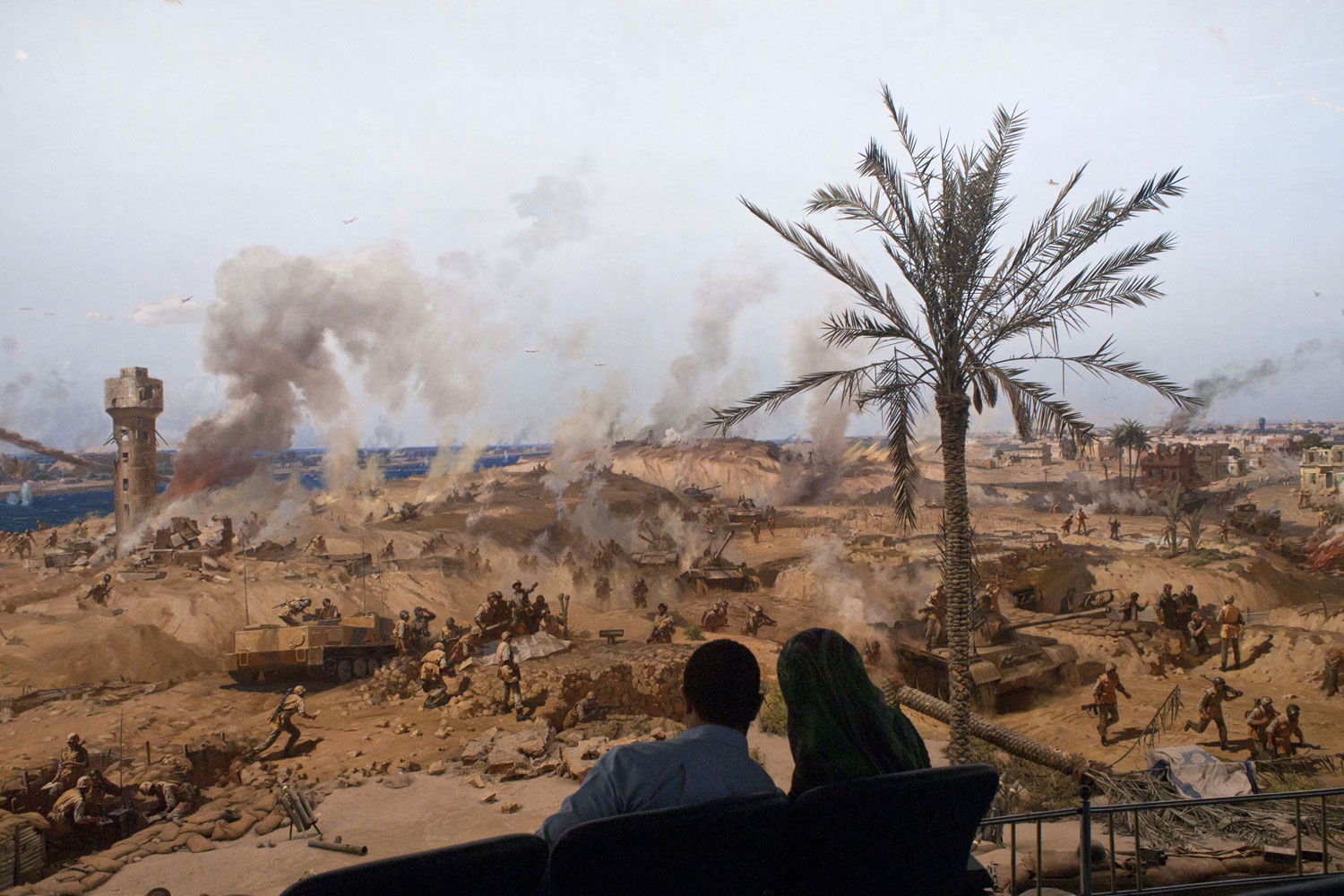 A couple sits near a panorama in Cairo depicting Egypt's war with Israel, April 2, 2011.