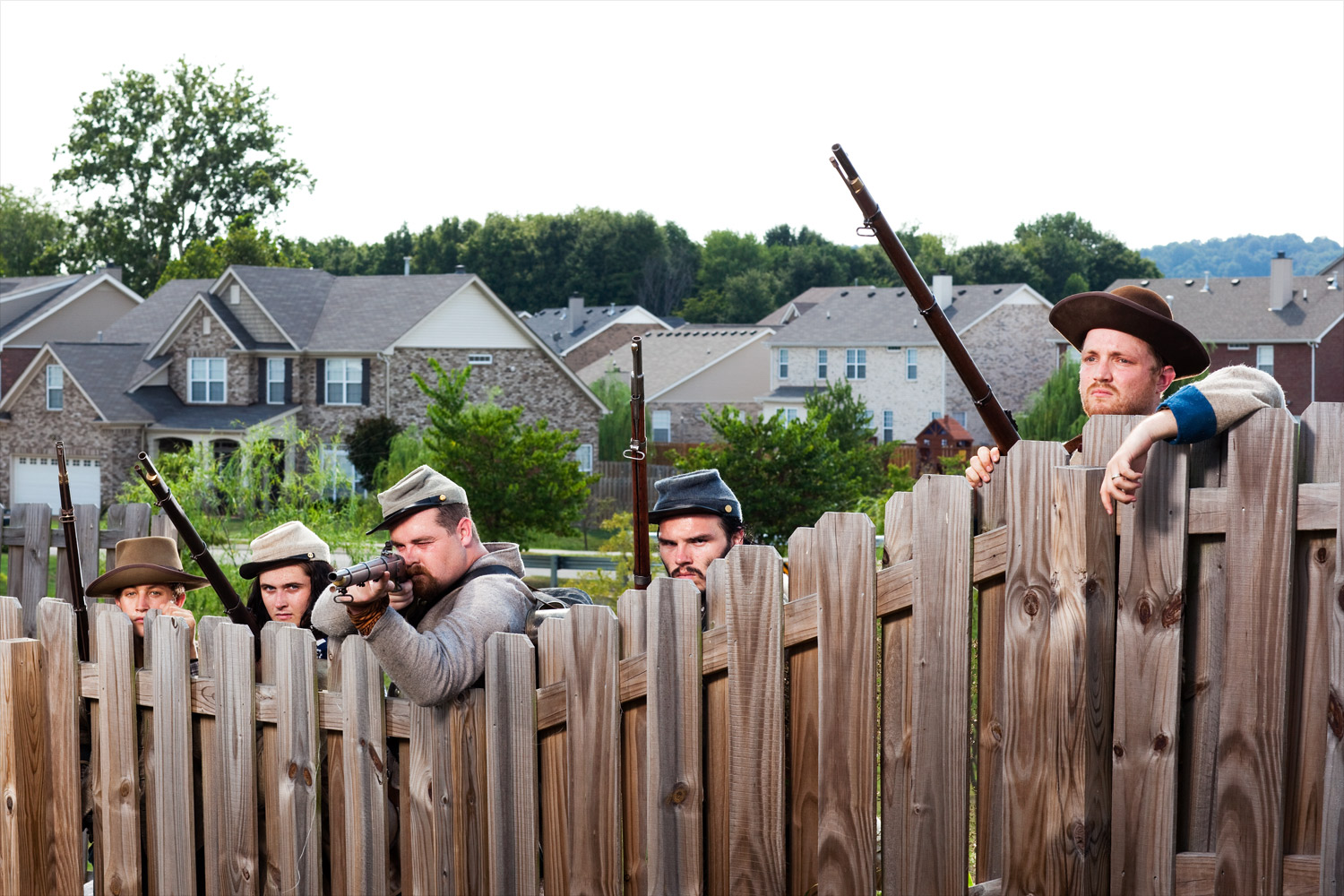 Spring Hill, Tn.                               Confederate reenactors line up behind the fence of a housing subdivision.