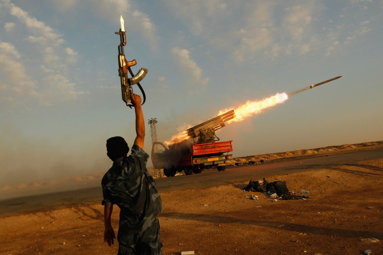 Ajdabiyah, Libya, April 14, 2011:  A rebel fighter celebrates as his comrades fire a rocket barrage toward the positions of troops loyal to Libyan ruler Muammar Gaddafi west of Ajdabiyah, Libya.