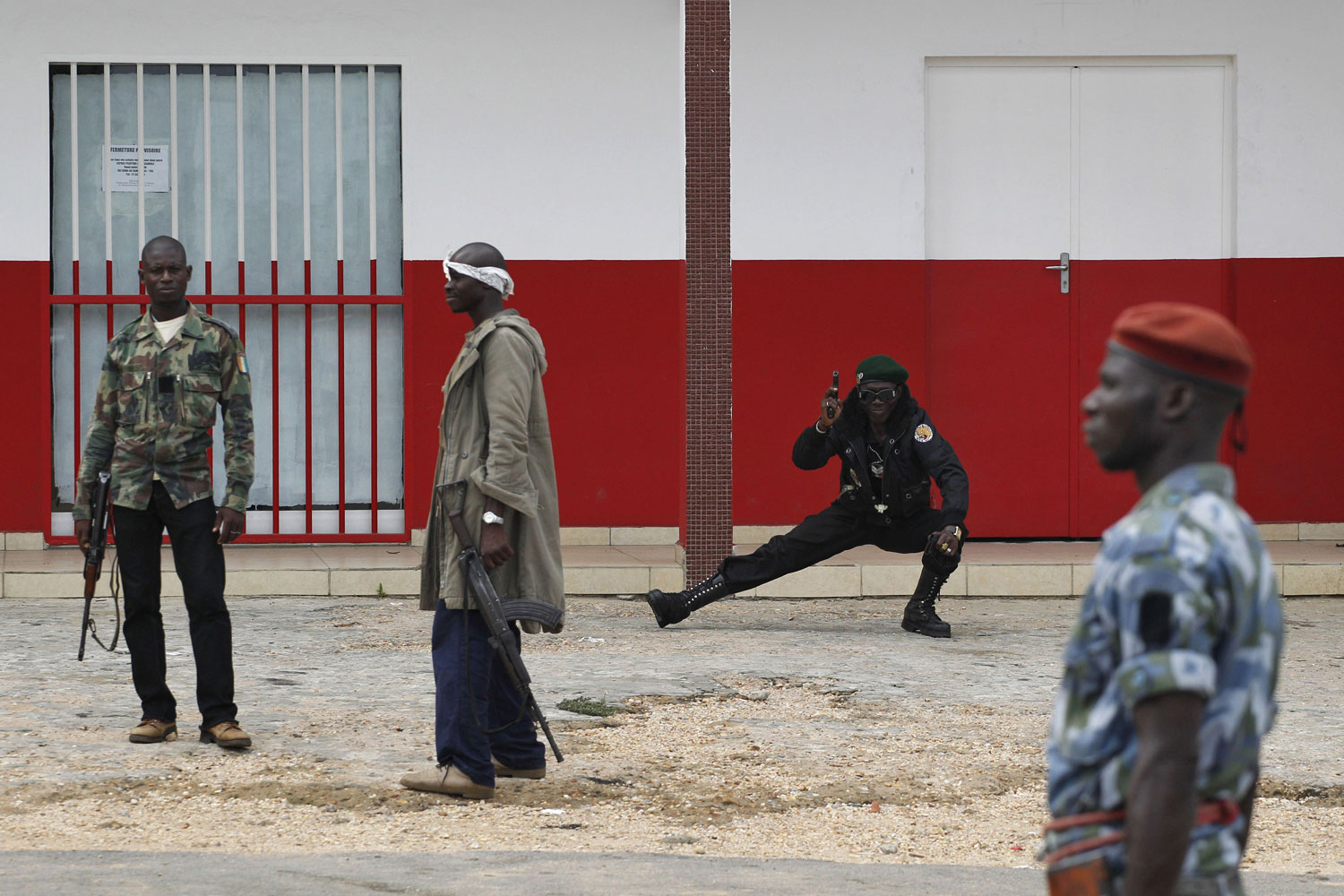 April 13, 2011. A republican forces soldier, second right, practices Tae Kwon Do moves while holding a pistol as he stands guard with other soldiers during a patrol in the Cocody neighborhood of Abidjan, Ivory Coast. The country's president is trying to establish order in the days after Ivory Coast's strongman was arrested, assuring the public that looting and gunfire will cease and life will soon return to normal.
