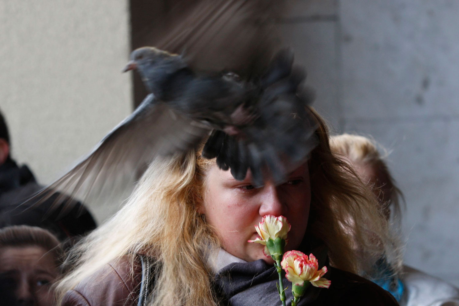 April 12, 2011. A woman mourns as a bird passes by her at the entrance to the Oktyabrskaya station of the Minsk subway in Belarus. The Belarusian government said a bomb placed under a bench at the subway station exploded on April11 as people were riding the trains during the evening rush hour. Twelve were killed.