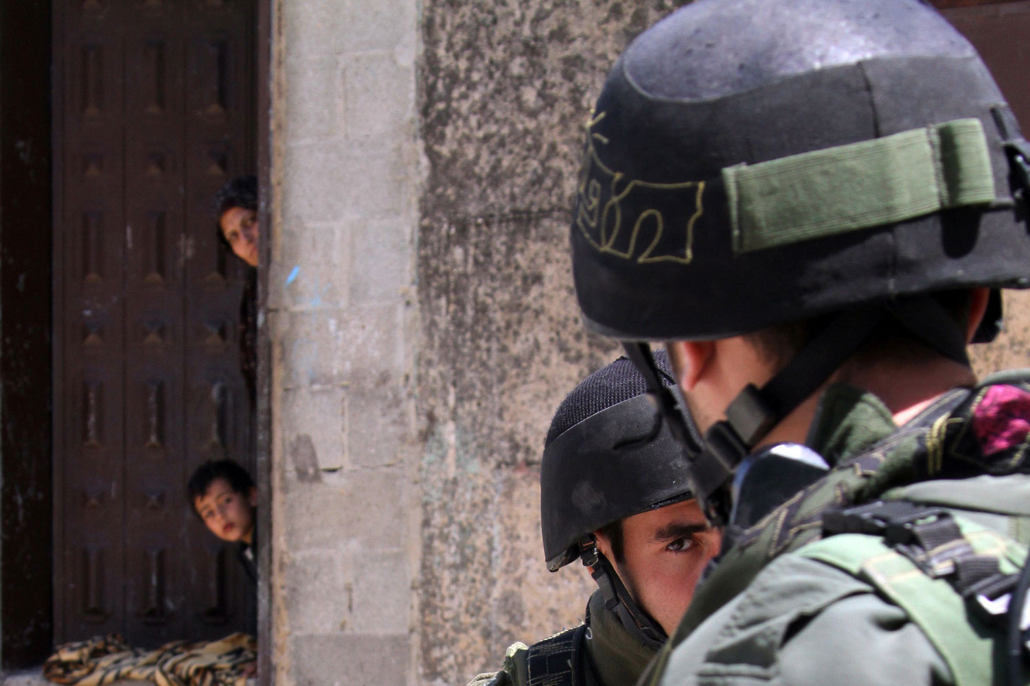 April 12, 2011. Palestinians watch Israeli troops in a military operation searching for suspects during a curfew in the West Bank village of Awarta, near Nablus. The Israeli army has repeatedly invaded the village following the murder of five members of one family in a nearby Jewish settlement.