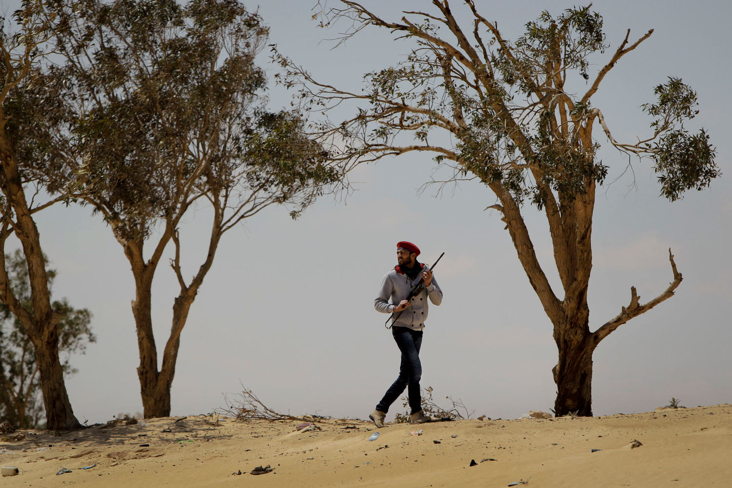 April 9, 2011. A rebel fighter in Libya walks on top of a sand dune to view smoke rising from the town of Ajdabiyah, which was mostly under the control of pro-Gaddafi forces. Government soldiers and rebels battled in the city's streets in the most serious Gaddafi-led push against rebel forces since NATO air strikes began.