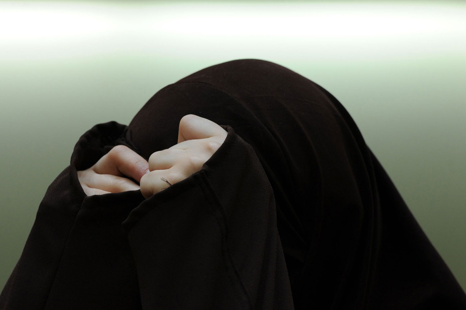 April 12, 2011. Defendant Vivian S. hides her face as she waits at the higher regional court in Munich, Germany. Seven men and a woman are accused of having distributed propaganda material supporting Al-Qaeda and Ansar al-Islam from August 2006 to March 2008.