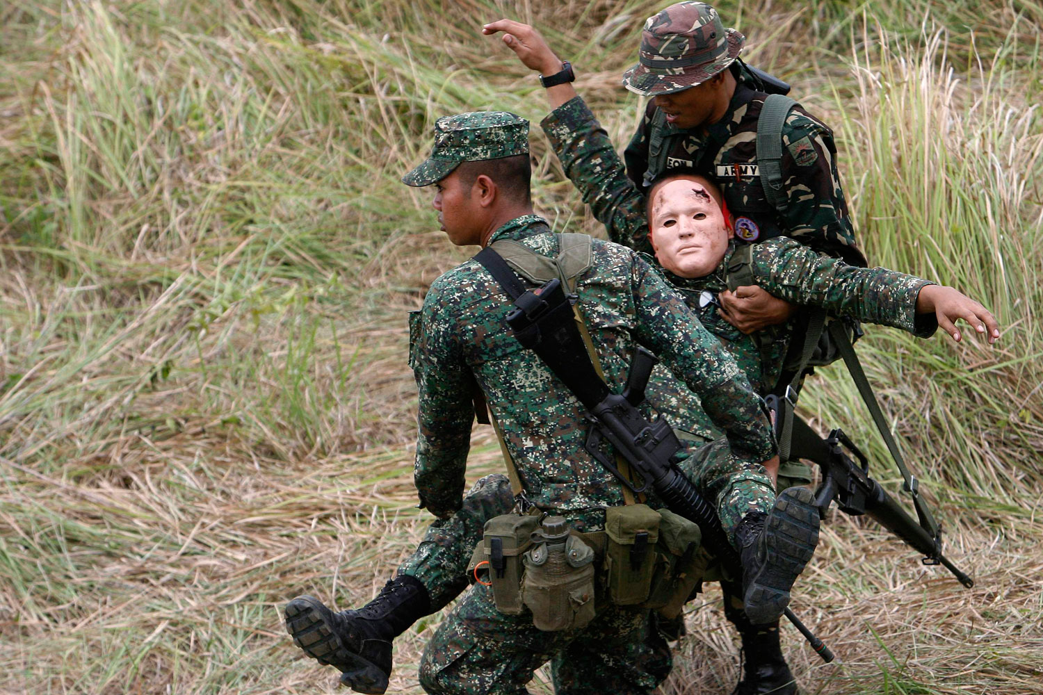 April 9, 2011. A soldier is carried by his comrades after being  wounded  in a convoy attack during a mock exercise as part of the U.S.-Philippines joint military exercises in Camp Magsaysay, Nueva Ecija, north of Manila. The United States has halved the number of soldiers taking part in war games in the Philippines this week due to emergency work in the disaster-hit areas of northeast Japan, officials said.