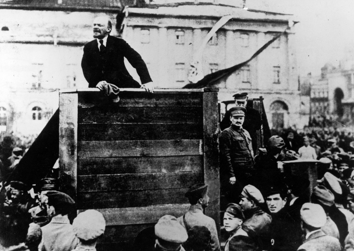 The Original Scene                               Taken within seconds of the preceding photo, this frame reveals that Lenin was joined that day by fellow Central Committee members Leon Trotsky, who stands in hat and mustache on the stairs to the right of the podium, and Lev Kamenev, who stands behind him. Perceived by Stalin as rivals to his power, both men were ultimately purged and their contributions to the revolution largely eliminated from the historical record. Though the photograph was widely published with the two men present during the 1920s, it was reproduced with stairs in their place for most of the Soviet era, even during the Gorbachev period.