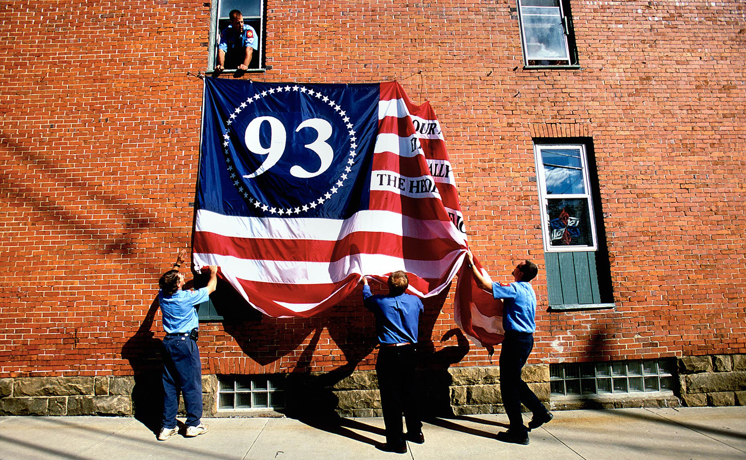Firemen take down a commemorative flight 93 flag from the side of a building in downtown Shanksville, PA. on the one year anniversary of 9/11.