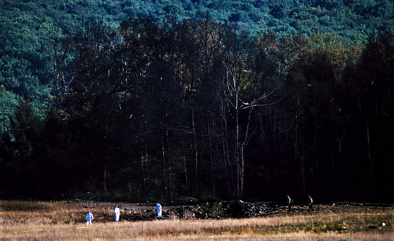 Men in white protective suits examine the crash site of Flight 93 with a scorched treeline behind them, Sept. 11, 2001. This was shot hours after the crash.