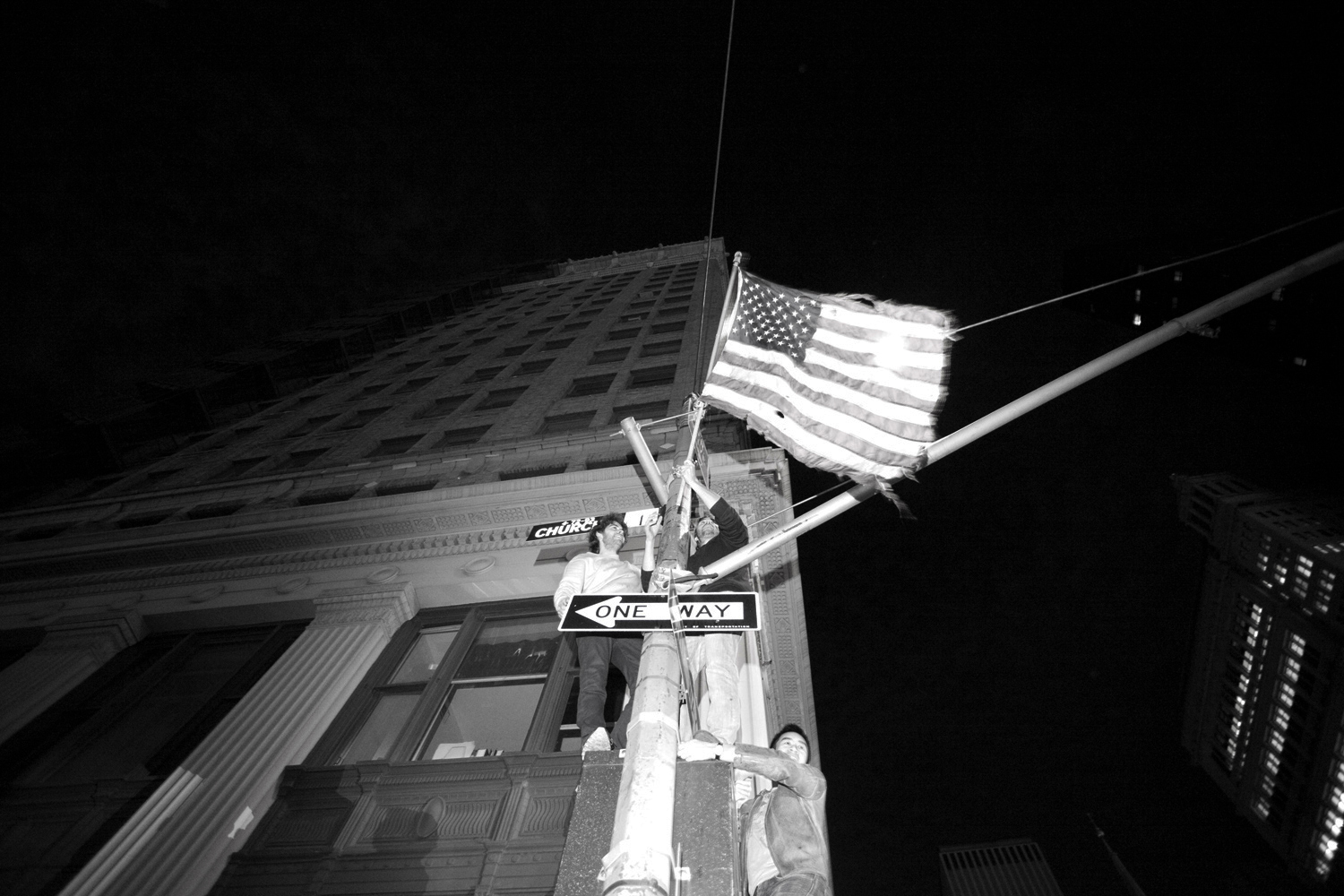 An excited young man raised the spirits of the crowd while waving a tattered flag over the streets.