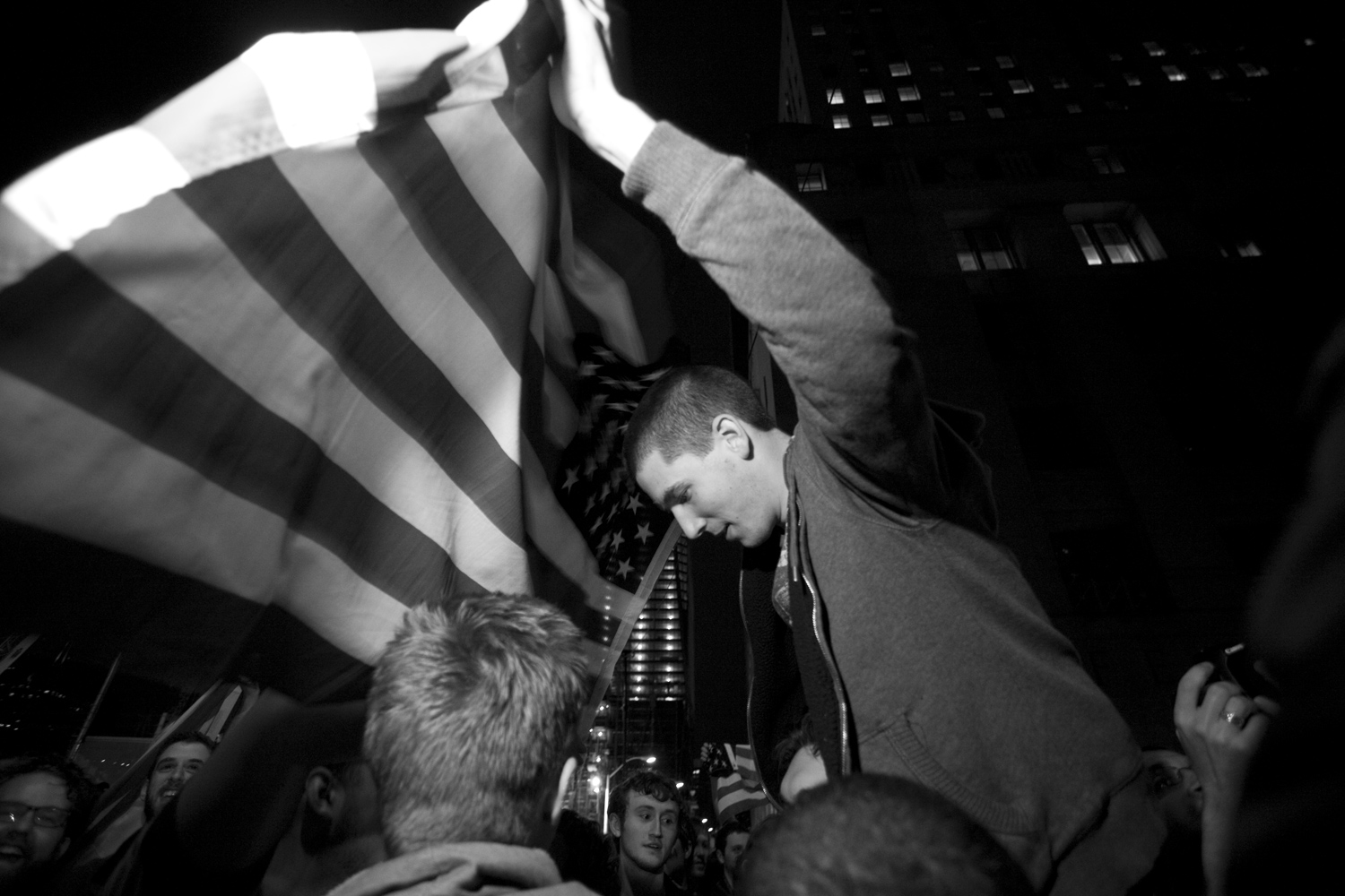 A young man gets a lift from his friend to wave a flag over the crowd.