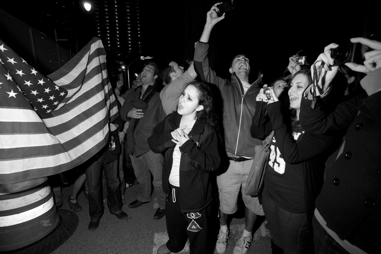 Emotions ran high among those gathering from solemn to excited. A young student Kathleen Lampert sings along to God Bless America with the crowd.